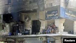 2015年8月叙利亚居民坐在被破坏的建筑物的阳台上。