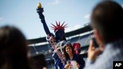 Brehisy Zuniga dari Meksiko berfoto dengan patung Liberty tiruan setelah menjalani upacara naturalisasi menjadi warga negara AS di Turner Field, Atlanta (16/9). (AP/David Goldman)