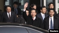 Japan's New Komeito's party leader Natsuo Yamaguchi (C) accompanied by the Japanese ambassador to China Masato Kitera (L) waves his hand as he walks out from the VIP exit of Beijing Capital International airport, January 22, 2013.