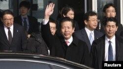 Utusan Jepang, Natsuo Yamaguchi (tengah) melambai saat tiba di bandara internasional di Beijing hari Selasa (22/1).
