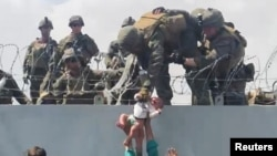 A baby is handed over to the American army over the perimeter wall of the airport for it to be evacuated, in Kabul, Afghanistan, August 19, 2021, in this still image taken from video obtained from social media. Video taken August 19, 2021.