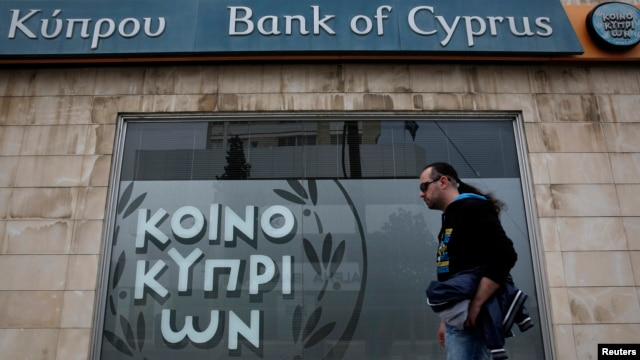 A man walks past a branch of Bank of Cyprus in Nicosia, March 31, 2013.