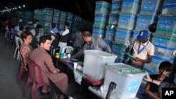 Komisi pemilu Afghanistan memilah kertas suara untuk diaudit di depan para pengamat internasional di kantor komisi pemilu di Kabul, Afghanistan, 27 Agustus 2014.