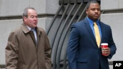 William Porter, right, one of six Baltimore city police officers charged in connection to the death of Freddie Gray, walks into a courthouse with his attorney Joseph Murtha for jury selection in his trial, Nov. 30, 2015, in Baltimore.