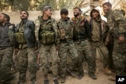 Para tentara Pasukan Demokratik Suriah yang didukung AS merayakan kemenangan merebut wilayah ISIS di Baghuz, Suriah, 19 Maret 2019.