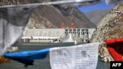 Prayer flags hang before Zangmu Hydropower Station in Gyaca county in Lhoka, or Shannan prefecture, southwest China's Tibetan Autonomous Region, Nov., 23, 2014.