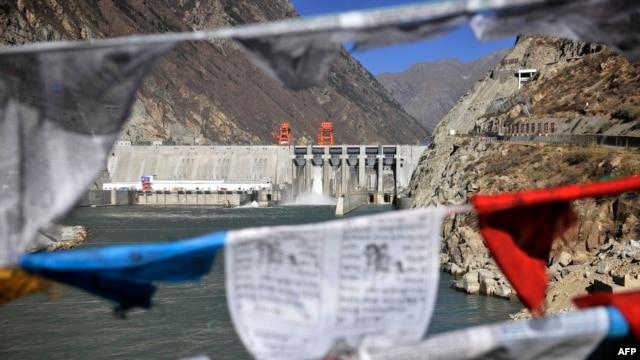 Prayer flags hang before Zangmu Hydropower Station in Gyaca county in Lhoka, or Shannan prefecture, southwest China's Tibetan Autonomous Region, Nov., 23, 2014.