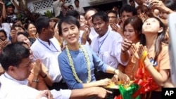 Aung San Suu Kyi, center, is surrounded by supporters after she cuts a ribbon to open the Aung San Jar-mon Library on Sunday, Aug. 14, 2011, in Bago, Burma.