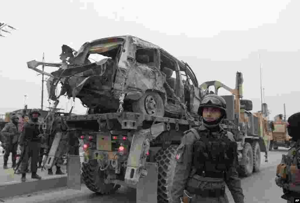 A U.S. military wrecker carries a vehicle away that was destroyed in a suicide car bomb attack on the Jalalabad-Kabul road in Kabul, Afghanistan, Dec. 27, 2013.