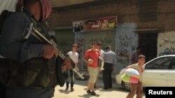 Warga Salah Edinne, Aleppo, bergegas meninggalkan tempat tinggalnya melintasi tentara Pembebasan Suriah yang tengah berjaga di tengah berkecamuknya pertempuran dengan pasukan pemerintah di kota itu (31/7). Pemerintah AS mengecam perintah presiden Assad un