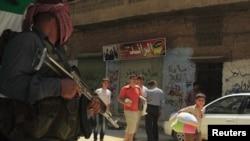 逃离的平民7月31日通过阿勒颇塞拉埃丁地区反政府军守卫军人的面前