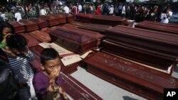 Warga melewati barisan peti jenazah yang disiapkan untuk para korban pesawat Hercules yang jatuh, di luar sebuah rumah sakit di Medan 1/7). (AP/Binsar Bakkara)