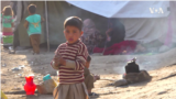 Children huddle together, waiting for food in an IDP camp in Kabul, Afghanistan.