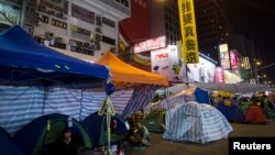 """A large banner reading """"We want universal suffrage"""" hung by pro-democracy protesters, is seen on a street light at a main street which they occupied, at Mongkok shopping district in Hong Kong, November 10, 2014."""