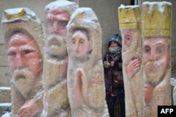 A girl smokes as she found a shelter from a snow fall behind sculptures depicting the nativity scene, in the center of western Ukrainian city of Lviv, Dec. 20, 2017.