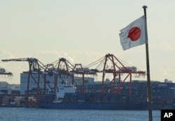 FILE - A Japanese flag is hoisted near the pier of a container terminal in Tokyo, Jan. 25, 2017. China is Japan's biggest trading partner and more than 30,000 Japanese companies have operations in the country.