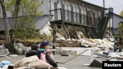 Mahasiswi beristirahat di depan gedung apartemen yang hancur akibat gempa bumi di kota Minamiaso di prefektur Kumamoto, Jepang selatan (16/4).