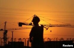 在夕阳映照下,一名建筑工人扛着锤子走在江苏南通某居民楼建筑工地。(2013年8月6日)