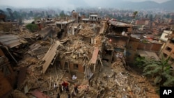 Rescue workers remove debris as they search for victims of earthquake in Bhaktapur near Kathmandu, Nepal, April 26, 2015. Nepal's parliament approved new laws to allow the government to spend billions of dollars pledged by foreign donors on earthquake reconstruction.