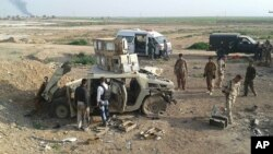 Курдские солдаты обследуют салон брошенного боевиками ИГИЛ бронетранспортера на присутствие химоружия. Киркук, Ирак. 16 марта 2015 г.