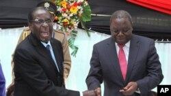 22일 경쟁자인 모건 창기라이 총리(오른쪽)와 악수하는 로버트 무가베 짐바브웨 대통령.