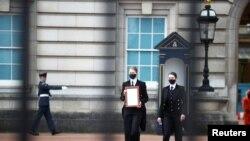 بکنگھم پیلس کے عملے کے ارکان شہزادہ فلپ کے انتقال کا سرکاری اعلان محل کے دروازے پر چسپاں کرنے کے لیے آ رہے ہیں۔