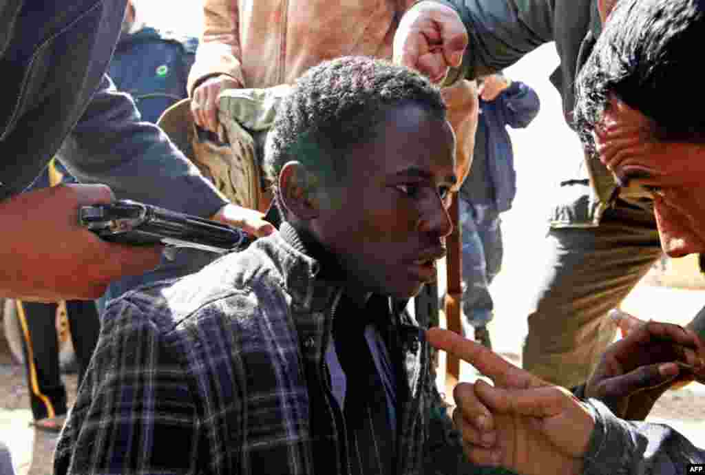 Rebels hold a young man at gunpoint, who they accuse of being a loyalist to Libyan leader Muammar Gaddafi. (Reuters/Goran Tomasevic)