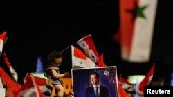 Pendukung Presiden Suriah Bashar al-Assad bersiap merayakan hasil pemilihan presiden di Damaskus, Suriah, 27 Mei 2021. (REUTERS / Omar Sanadiki)