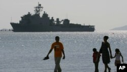 FILE - A Filipino family stroll the beach at Subic Bay as the USS Harpers Ferry approaches to dock, Feb. 17, 2006.
