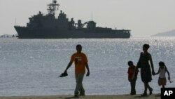 FILE - A Filipino family stroll the beach at Subic Bay as the USS Harpers Ferry approaches to dock.