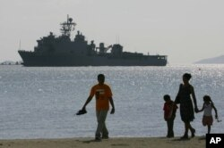 Một gia đình người Philippines đi dạo trên bãi biển tại vịnh Subic. Phía sau là tàu USS Harpers Ferry của hải quân Mỹ (ảnh tư liệu).