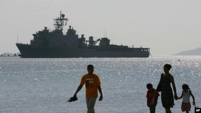 Một gia đình người Philippines đi dạo trên bãi biển tại Vịnh Subic. Phía sau là chiến hạm USS Harpers Ferry của hải quân Hoa Kỳ. (Ảnh tư liệu chụp ngày 17/2/2006).