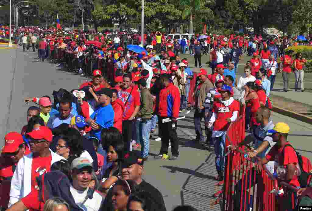 Supporters of Venezuela's late President Hugo Chavez line up to view his body in state at the Military Academy in Caracas, March 7, 2013.