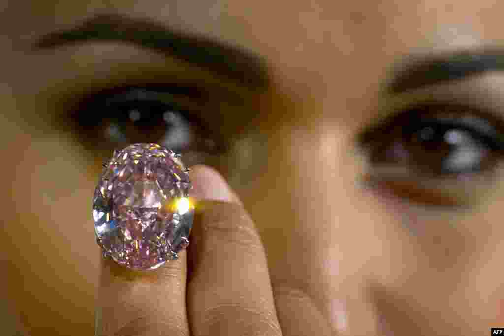 A model shows a 59.6-carat pink diamond that will be auctioned by Sotheby's in the Swiss city of Geneva in November at a record asking price of $60 million (49 million euros).