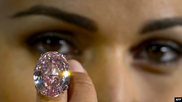 FILE - A model shows Pink Star, the 59.6-carat pink diamond auctioned by Sotheby's in the Swiss city of Geneva, during a press preview.