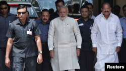 India's Prime Minister Narendra Modi (C) walks to speak with the media as he arrives to attend his first Parliament session in New Delhi, June 4, 2014.