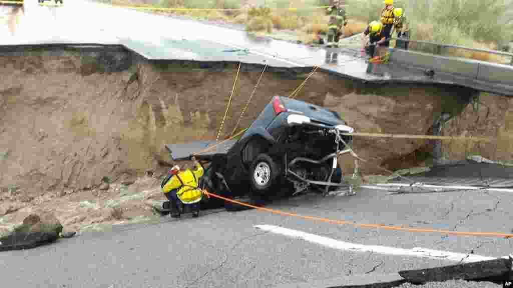 ក្នុងរូបភាពផ្តល់ដោយ CAL FIRE/Riverside County Fire Department បង្ហាញពីក្រុមជួយសង្គ្រោះប្រតិបត្តិការជួយរថយន្ត Pick Up មួយគ្រឿង ដែលបានធ្លាក់ចូលទៅក្នុងរណ្តៅ ដែលបង្កឡើងដោយការបាក់រលំនៃស្ពាននៅផ្លូវហាយវ៉េ Interstate 10 ក្នុងមជ្ឈមណ្ឌល Desert Center ក្នុងរដ្ឋ California កាលពីថ្ងៃទី១៩ ខែកក្កដា ឆ្នាំ២០១៥។