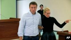 Pemimpin oposisi Rusia, Alexei Navalny (kiri) dan istrinya Yulia meninggalkan ruang pengadilan di Kirov, Rusia (16/10).