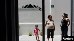 FILE - Salvadoran Yesenia Elizabeth Orellana, 40, who is pregnant, holds hands with her daughter Valentina, 3, as her friend Mirna Laines, also pregnant, looks on at the Catholic migrant shelter in San Luis Potosi.