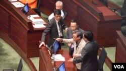 獨立議員黃毓民(持鉛筆者)拒絕保安人員將他帶離會議廳。(美國之音 湯惠芸攝)