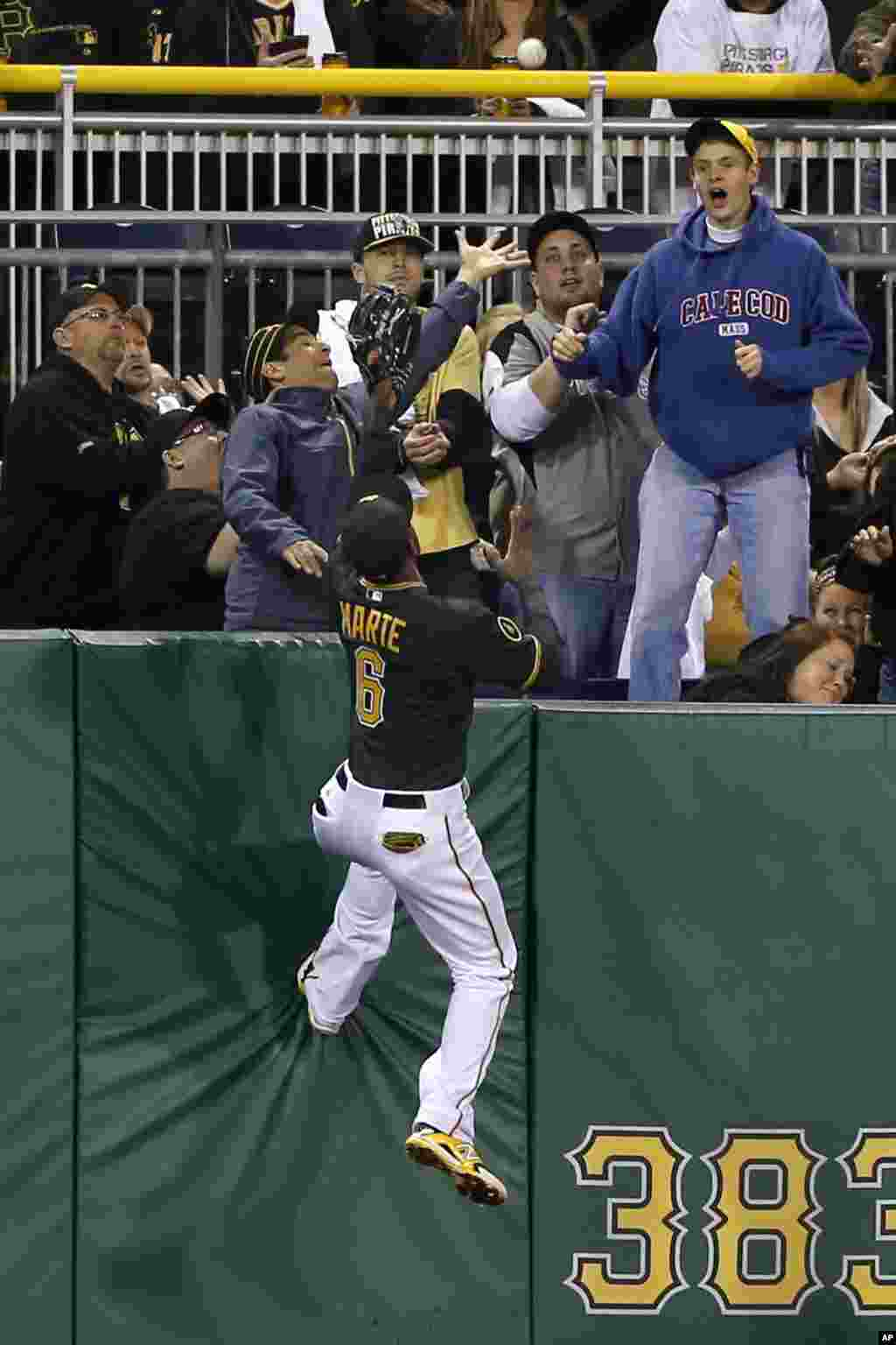 Pittsburgh Pirates left fielder Starling Marte (6) climbs the wall chasing the ball as fans reach for the home run ball hit by Toronto Blue Jays' Colby Rasmus in the fourth inning of a baseball game in Pittsburgh, Pennsylvania, USA, May 2, 2014.