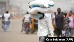 Un homme porte des sacs de riz sur la tête à une frontière entre Abuja et l'État de Nasarawa le 30 mars 2020.