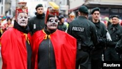 FILE - German police officers stand guard as two carnival revelers wait for the start of the traditional Rose Monday carnival parade in the western German city of Cologne, Feb. 16, 2015.
