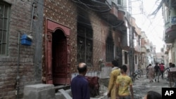 FILE - Residents look at the house of a family belonging to the Ahmadi sect, which was torched by angry mob in Gujranwala, Pakistan, July 28, 2014.