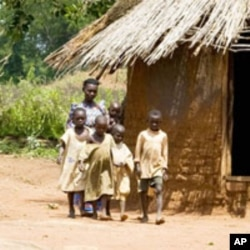 In Uganda, Victoria Ddundu, 46, a widow and mother of 5, walks with her children in a village in Palisa. Her family relies on the food she grows.