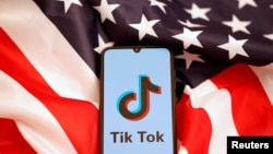 美國國旗和手機上顯示的Tiktok標識。