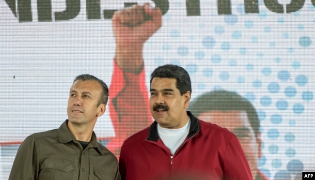 FILE - Venezuelan President Nicolas Maduro, right, and his Vice President Tareck El Aissami participate in a rally with workers of PDVSA state-owned oil company in Caracas, Jan. 31, 2017.