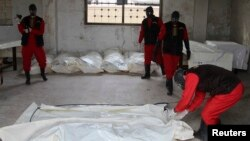 FILE - Workers wrap the bodies of dead fighters loyal to Syrian President Bashar al-Assad at a morgue in Aleppo, Oct. 30, 2014. The opposition Free Syrian Army said it killed the men near Aleppo city and that some of the dead had Iranian and Afghan nationalities.