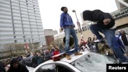 Demosntranti skaču po policijskim kolima tokom jučerašnjeg protesta zbog smrti Fredija Greja