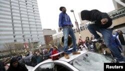 Para demonstran melompati dan merusak mobil polisi dalam aksi protes rusuh di Baltimore, Sabtu (25/6).